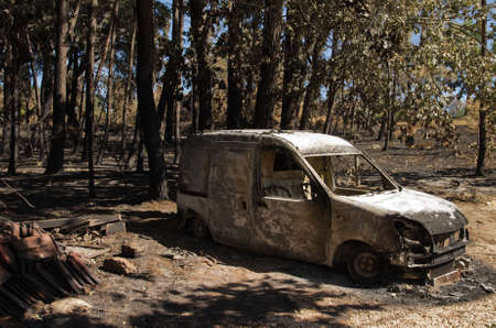 Small van burnt to the ground next to also burnt forest trees at a small village of Pedrogao Grande municipality named Lameira Cimeira. Caused by a massive forest fire. Portugal.