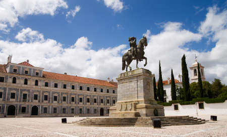 Statue of King John IV (D. Joao IV) on horseback in front of Ducal Palace and under a blue and white clouded sky. Vila Vicosa, Alentejo, Portugal.