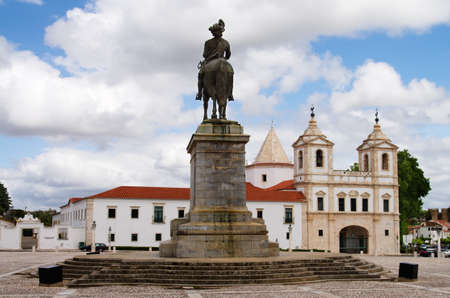 Statue of King John IV (D. Joao IV) facing the church and monastery of Agostinhos under a blue and white clouded sky. Vila Vicosa, Alentejo, Portugal. Stock Photo
