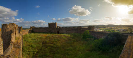 Main space of Terena castle. A field of green weeds and empty walls under a blue clouded sky near the end of the day. Alentejo, Portugal.
