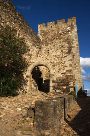 Pathway, arch and gate at the entrance of Terena castle under a strong blue sky. Alentejo, Portugal.