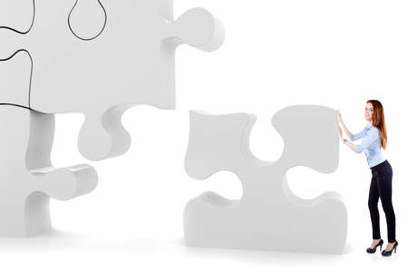 assembly: Attractive business woman pushing a puzzle piece