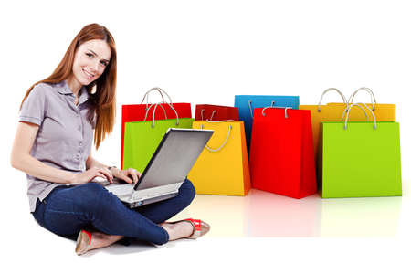 young butiful woman using a laptop for online shopping with 3d shopping bags in the background photo