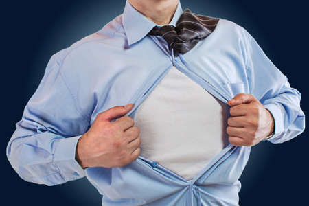 Young business man tearing apart his shirt revealing a superhero suit Stock Photo