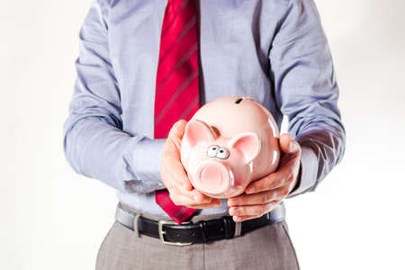 business man holding a pig bank - economy savings photo