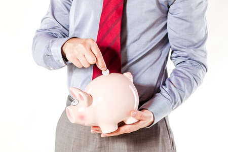 deposit slip: business man holding a pig bank - economy savings
