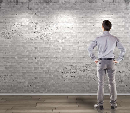 white walls: young attractive business man in front of a vintage old blank wall Stock Photo