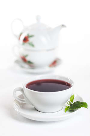 english tea: porcelain cup and teapot  on white background
