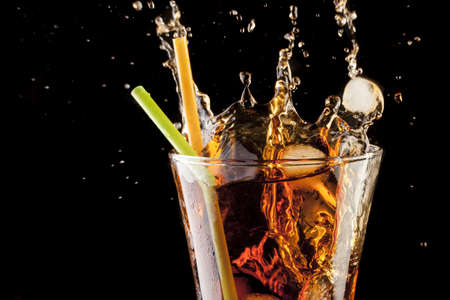 fresh cola juice and ice cubes splash in a glass on black background Stock Photo