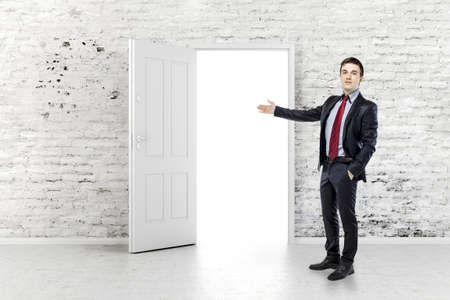 business man in front of an open door in a vintage white brick wall photo