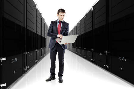 businessman holding a laptop with servers in the background photo