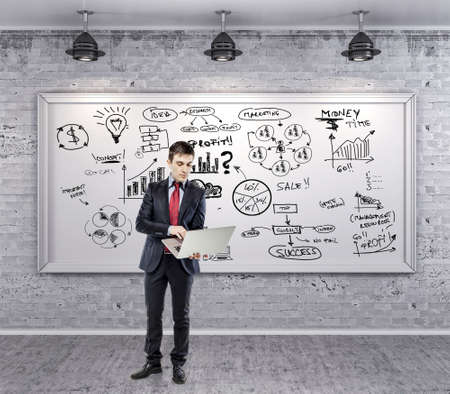 market research: businessman in suit and business plan on grunge wall