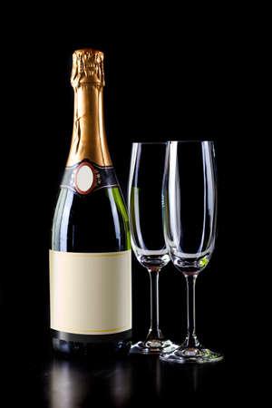 fles champagne en twee glazen op een zwarte achtergrond Stockfoto