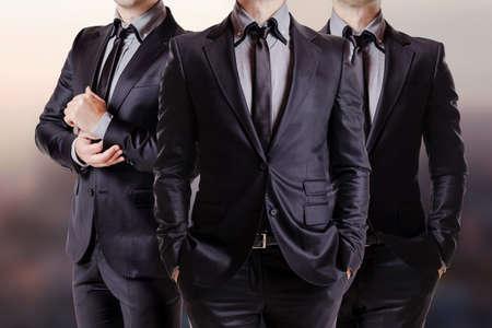 bata blanca: Cerrar una imagen de tres hombres de negocios en traje negro