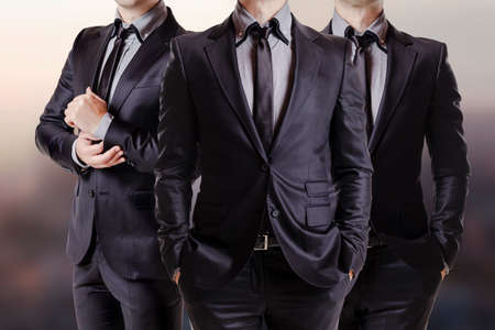 formal dress: Close up image of three business men in black suit