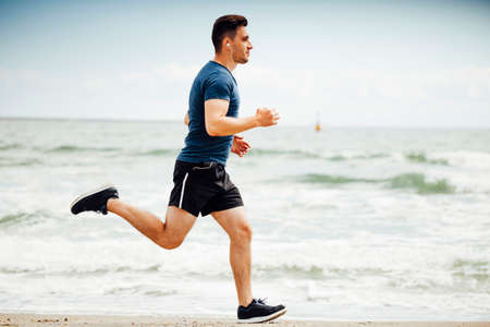 Man running on sunny; beach
