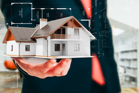 architecture: Close-up image of businessman holding a 3d house, architecture project
