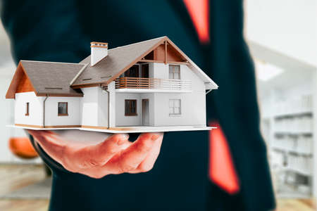 modern house: Close-up image of businessman holding a 3d house, architecture project