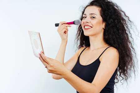 Young beautiful model with curly hair using beauty products