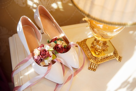 Chaussures de mariage de la mariée avec des fleurs sous le soleil d'été Banque d'images