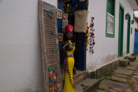 Handcraft Shop with Woman Sculpture in Yellow Dress and Red Hat