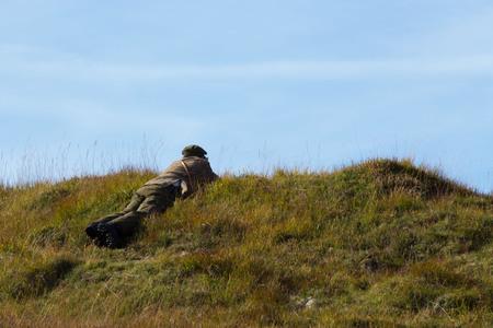 Deerstalker Lying on Hill in Scottish Highlands