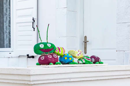 A funny Caterpillar made of stones on a balcony in Kamari, Santorini, Greece