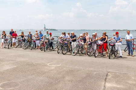 Cycling fun on Governors Island with the Statue of Liberty in the background, New York, United States