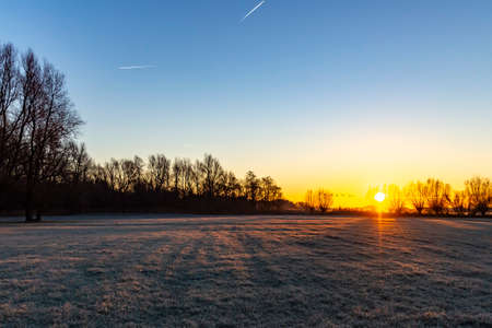 The pasture next to lake Zoetermeerse plas is frosted when the sun rises and the sky gets wonderful colors