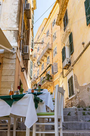 The tables are ready for the guests in the small streets of Corfu Town, Corfu, Greece