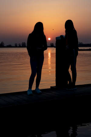 Two young women relaxing during sunset on a landing stage at the Lake Zoetermeerse Plas in Zoetermeer, The Netherlands 3 Stock Photo
