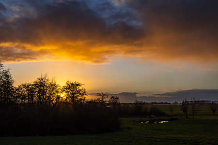 Clouds are beautifully lit by the setting sun that slowly disappears behind the shrubbery in Geer Polder near Zoetermeer, Netherlands Stock Photo