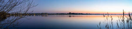 A panorama photo during the Blue hour on a allmost windless evening with a smooth lake Zoetermeerse Plas, Netherlands