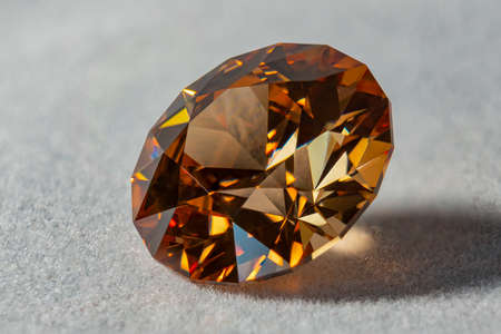 Photo of a Champagne colored Cubic Zirconia gemstone, cut in the shape of a Standard Round Brilliant (design PvNiel) on a white velvet surface
