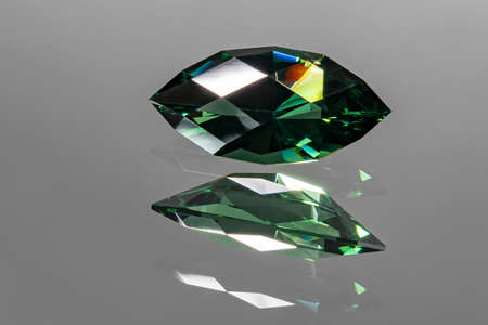 Photo of a dark green colored Prasiolite gemstone, cut in the shape of a Beginner marquise, with reflection in the mirror on which it is placed. The refraction of the light gives many colors on the facets