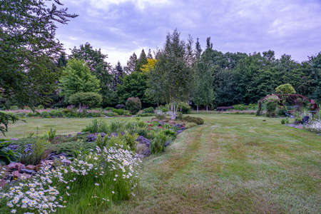 The colors of the flowerbeds seem to get more intense during the evening twilight in this beautifully landscaped garden with a great diversity of trees and flowering shrubs near the village of Harkstede in Groningen