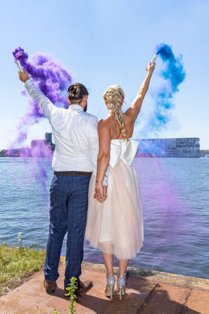 Photo of a beautiful bridal couple with colored torches in their hands along the Noordelijke IJ-oevers West in Amsterdam