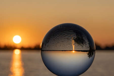 The rising sun is reflected in the water of lake Zoetermeerse Plas and inverted in the Lens Ball