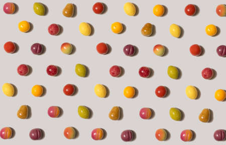 Flat lay isometric pattern of small marzipan fruit shaped candies in different colors and shapes - lemon, lime, pear, peach, plum, orange, apple against light background.