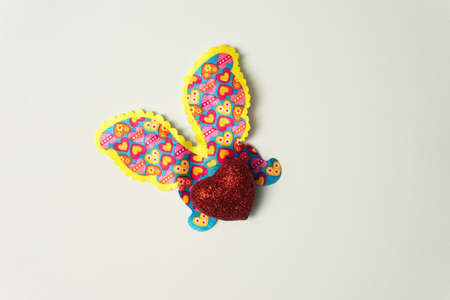Glittery heart shaped body with butterfly wings - butterfly against nice light green background.