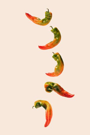 Abstract concept of fresh organic unique shape pepper falling down on a beige background.