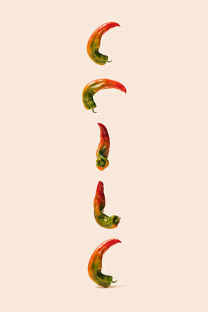 Modern concept of yummy organic unique shape peppers floating in the air and and follwing down on a beage background. Stock fotó