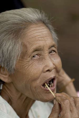 rotten teeth: Portrait of an old Asian woman with gray hair