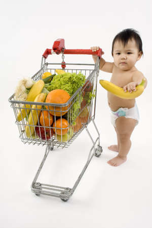 Baby pushes a shopping cart with fruit and vegetables photo