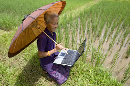 Old Asian with laptop photo
