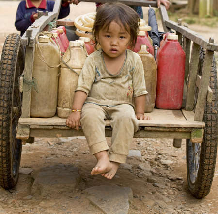 Child with gasoline can sitting on a cart, Laos