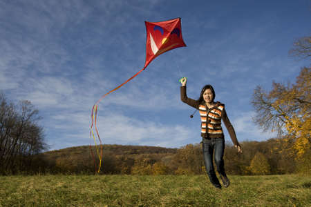 kite flying: fly a kite, teenager in fall weather in nature Stock Photo
