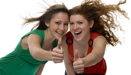 jubilation: lucky teenagers show joy, two girls with blowing hair Stock Photo