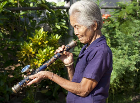 pipe smoking: old Asian woman with opium pipe