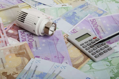 Energy waste, symbolised with thermostat, pocket calculator and money Stock Photo - 6036260
